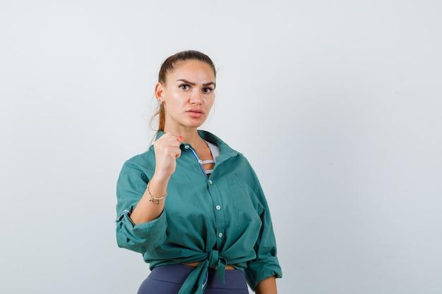 Молодая дама показывает кулак в рубашке, штанах и смотрит задумчиво, вид спереди.