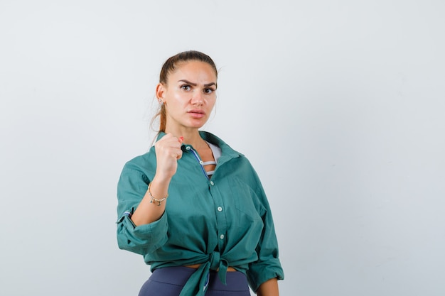 Young lady showing fist in shirt, pants and looking wistful , front view.