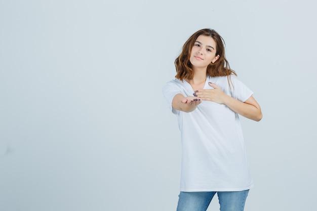 T- 셔츠, 청바지에 제스처를주고 귀여운, 전면보기를 보여주는 젊은 아가씨.