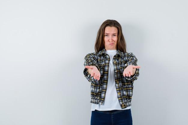 Tシャツ、ジャケット、ジーンズで唇を湾曲させ、物思いにふける、正面図を見てジェスチャーを与える若い女性。