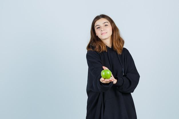 特大のパーカー、ズボンでリンゴを保持し、楽しい、正面図を見てジェスチャーを与える若い女性。