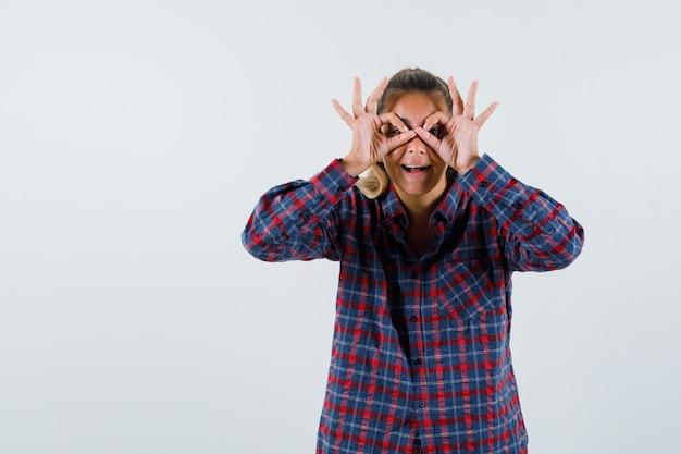 Giovane signora che mostra il gesto di vetri in camicia controllata e che sembra allegra. vista frontale.