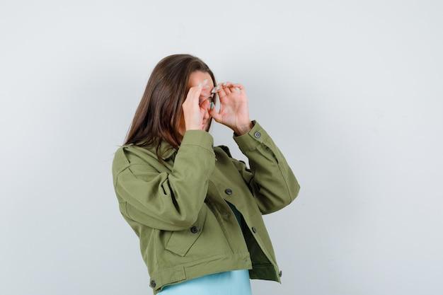 Tシャツ、ジャケットで眼鏡のジェスチャーを示し、おかしな顔をしている若い女性。正面図。