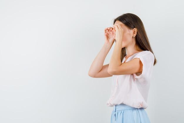 Tシャツ、スカート、集中して見えるメガネジェスチャーを示す若い女性。