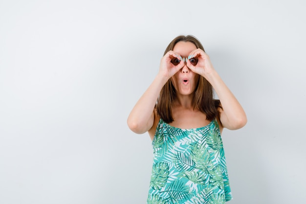 Young lady showing glasses gesture and looking wondered , front view.