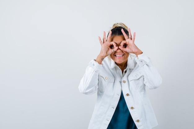 Giovane signora che mostra il gesto degli occhiali in camicia, giacca bianca e sembra divertita, vista frontale.