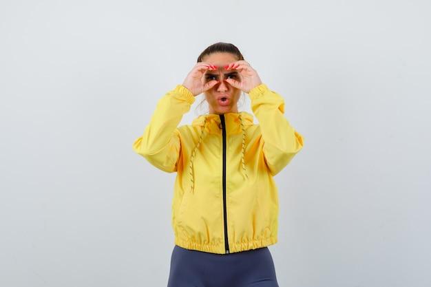 Giovane signora che mostra il gesto degli occhiali in giacca gialla e sembra divertente, vista frontale.