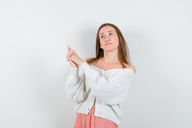 カーディガンとスカートで自信を持って孤立しているように見える銃のジェスチャーを示す若い女性