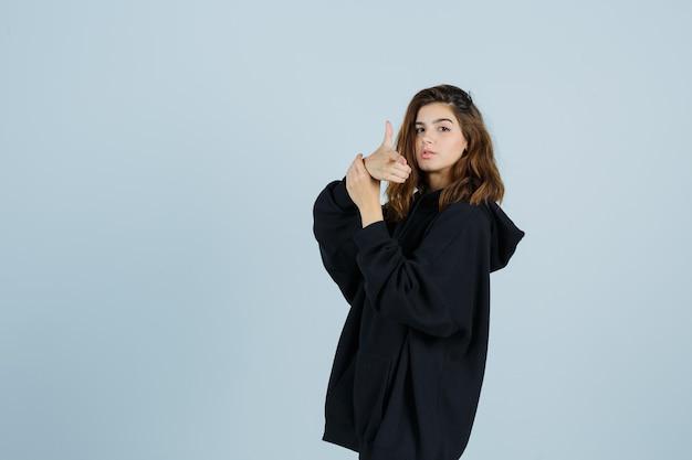 Молодая леди показывает жест пистолета в негабаритной толстовке с капюшоном, штанах и выглядит серьезно, вид спереди.