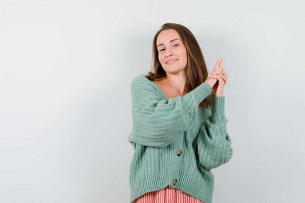 ウールのカーディガンで銃のジェスチャーを示し、陽気に見える若い女性、正面図。