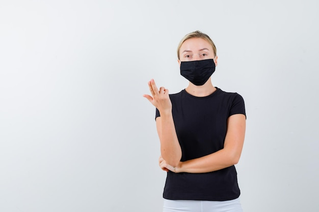 Young lady showing gun gesture in t-shirt, pants, medical mask and looking confident