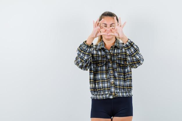 Giovane signora che mostra il gesto del cuore in camicia a quadri, pantaloncini e sembra allegra. vista frontale.