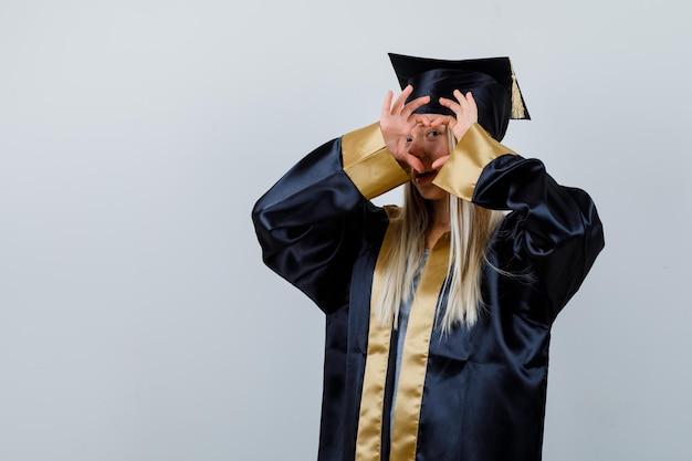 Молодая леди показывает жест сердца в академической одежде и выглядит мило