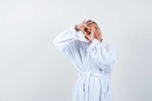 バスローブでハートのジェスチャーを示し、かわいく見える若い女性