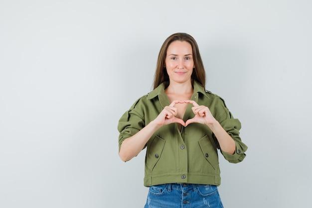 Молодая леди показывает жест сердца в зеленых шортах пиджака и выглядит мило
