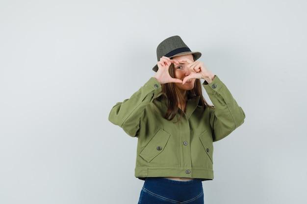 Молодая дама показывает жест сердца в шляпе пиджака и брюк и выглядит весело