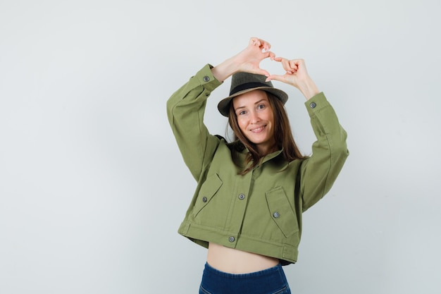 Молодая леди показывает жест сердца в шляпе и брюках пиджака и выглядит весело