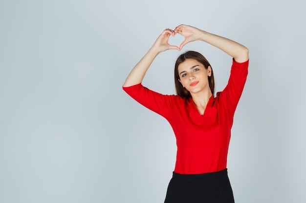 赤いブラウス、スカートでハートのジェスチャーを示し、きれいに見える若い女性
