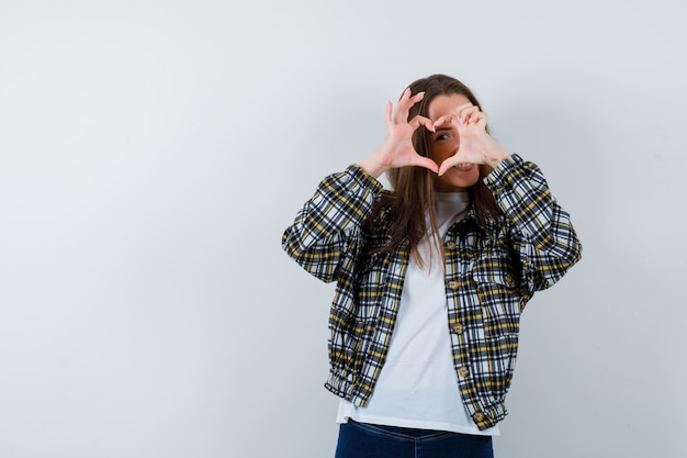 Tシャツ、ジャケットでハートのジェスチャーを示し、嬉しそうに見える若い女性。正面図。