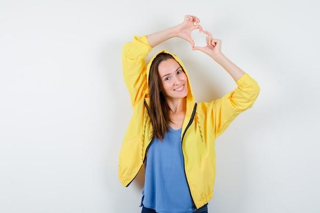 Tシャツ、ジャケットでハートのジェスチャーを示し、陽気に見える若い女性。正面図。