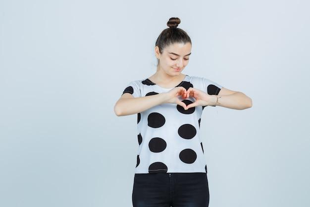Молодая дама показывает жест сердца в футболке, джинсах и выглядит мило. передний план.
