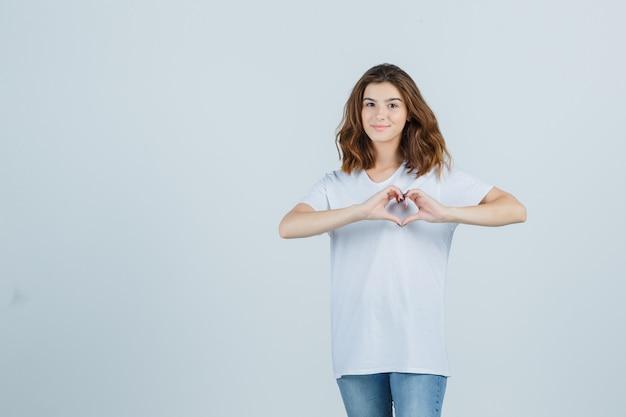Молодая дама показывает жест сердца в футболке, джинсах и выглядит довольно. передний план.