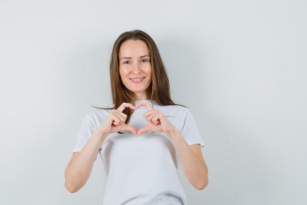 Молодая леди показывает жест сердца в белой футболке и выглядит весело