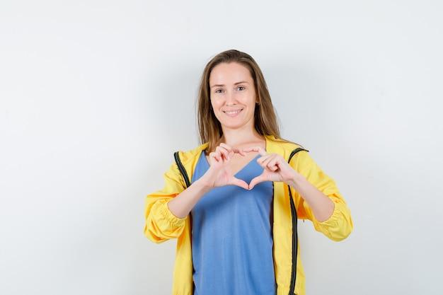 Giovane signora che mostra gesto del cuore e sembra felice, vista frontale.