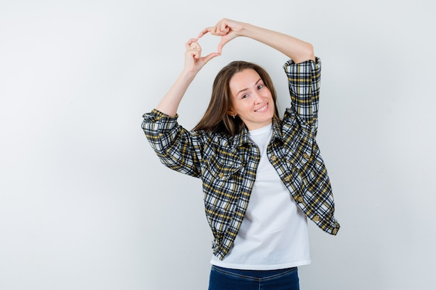 Молодая леди показывает жест сердца над головой в футболке, куртке, джинсах и выглядит мило. передний план.