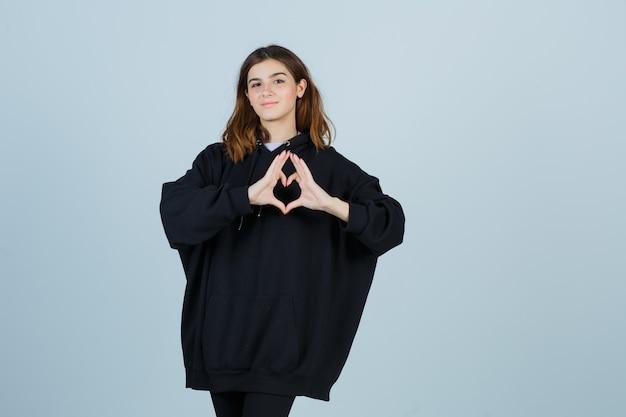 Giovane donna che mostra il gesto del cuore in felpa con cappuccio oversize, pantaloni e sembra carina. vista frontale.
