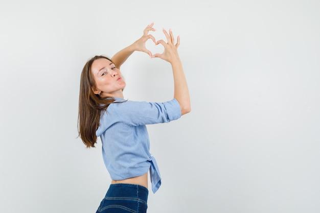 青いシャツで唇をふくれっ面、心臓のジェスチャーを示す若い女性