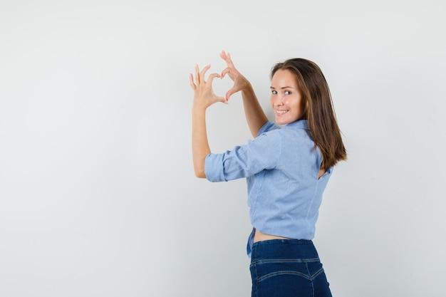 Giovane signora che mostra il gesto del cuore e sorridente in camicia blu