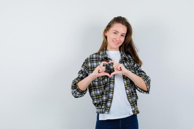 Giovane signora che mostra il gesto del cuore in maglietta, giacca, jeans e sembra beata. vista frontale.