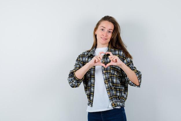 Giovane signora che mostra il gesto del cuore in t-shirt, giacca, jeans e carino, vista frontale.