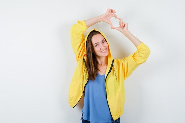Giovane signora che mostra il gesto del cuore in maglietta, giacca e sembra allegra. vista frontale.