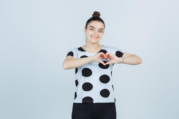 Giovane signora che mostra il gesto del cuore in maglietta, jeans e che sembra carina. vista frontale.