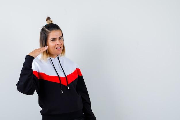パーカーのセーターで高さのサインを示し、陽気に見える若い女性