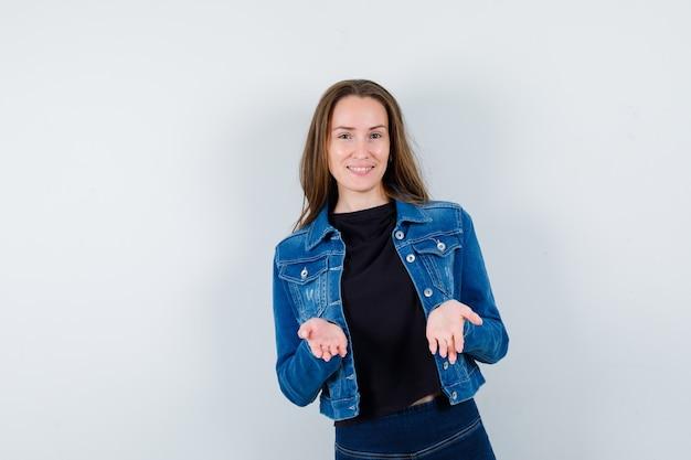 Giovane donna che mostra gesto impotente in camicetta, giacca e sembra sicura, vista frontale.