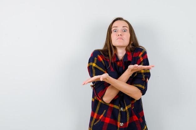 캐주얼 셔츠에 무력한 제스처를 보여주는 젊은 아가씨 혼란, 전면보기를 찾고.