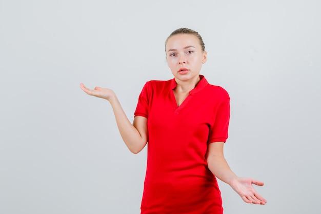 赤いtシャツで無力なジェスチャーを示し、困惑している若い女性