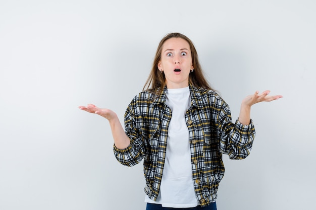 Tシャツ、ジャケットで無力なジェスチャーを示し、困惑しているように見える若い女性。正面図。
