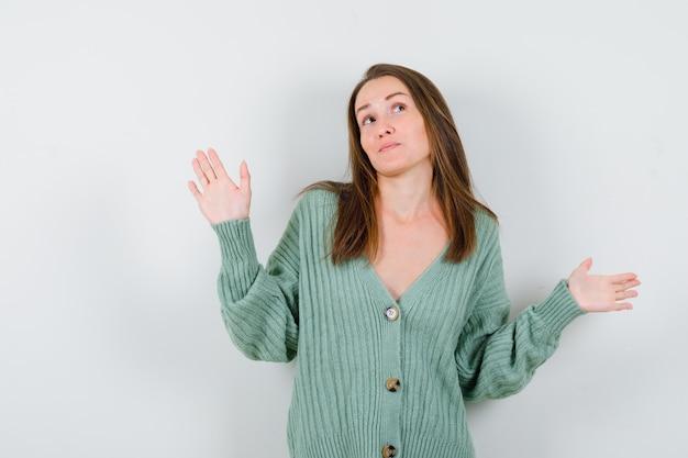 ウールのカーディガンで無力なジェスチャーを示し、躊躇している若い女性。正面図。