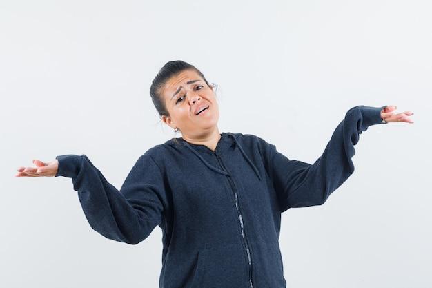 Giovane signora che mostra gesto impotente in giacca e sembra infelice