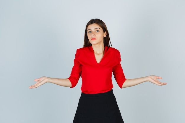 Giovane donna che mostra gesto impotente in camicetta rossa, gonna nera e sembra perplessa