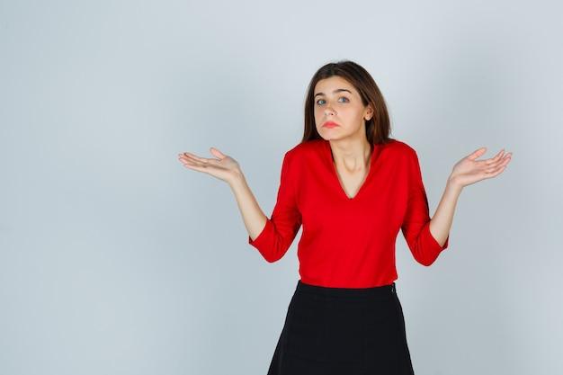 Giovane signora che mostra gesto impotente in camicetta rossa, gonna e sguardo stressato