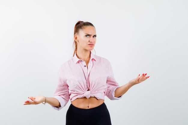 Giovane donna che mostra gesto impotente in camicia, pantaloni e sguardo perplesso