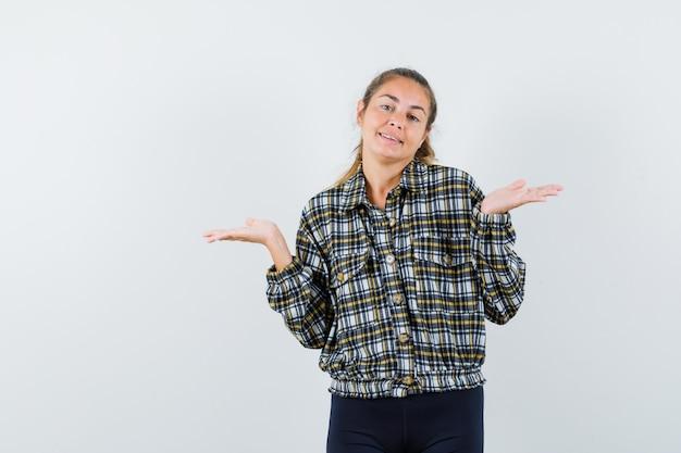Giovane signora che mostra gesto impotente in camicia, pantaloncini e sguardo confuso, vista frontale.