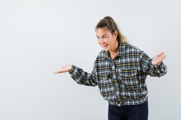 Giovane donna che mostra gesto impotente in camicia, pantaloncini e sembra ottimista. vista frontale.