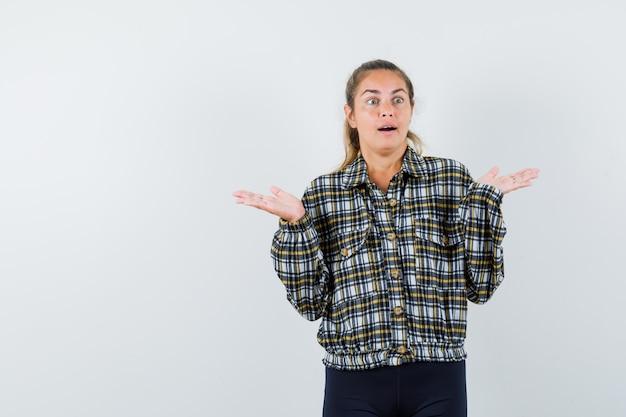 Giovane donna che mostra gesto impotente in camicia, pantaloncini e guardando perplesso, vista frontale.