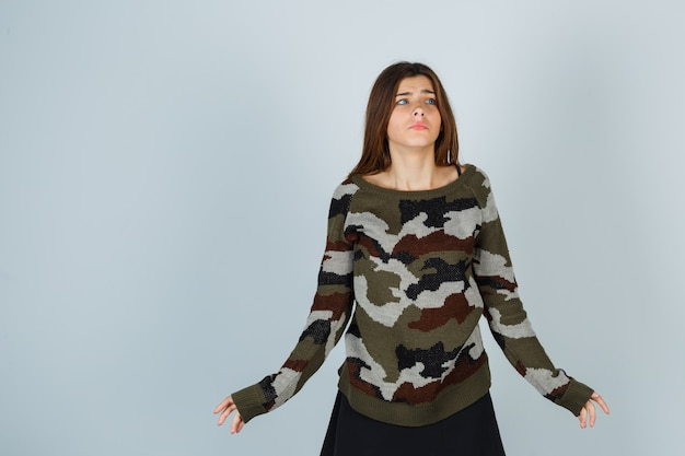 Young lady showing helpless gesture in sweater and looking anxious